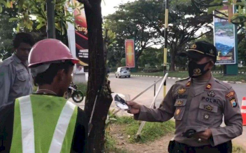 BAGI MASKER. Kapolsek Kawasan Bandara Sultan Hasanuddin Iptu Asep Widianto membagikan masker di sekitar Bandara Internasional Sultan Hasanuddin Makassar, Minggu (5/7/2020). foto: anas/pluz.id