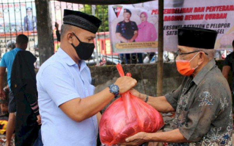 DAGING KURBAN. Danyon C Pelopor, Kompol Nur Ichsan (kiri), menyerahkan daging kurban kepada salah satu penerima di Mako Yon C Pelopor, Bone, Jumat (31/7/2020). foto: istimewa