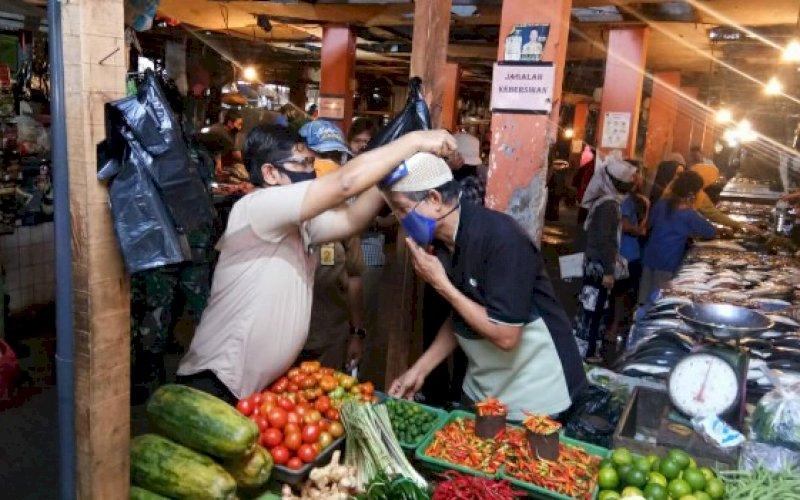 GUNAKAN MASKER. Direktur Operasional PD Pasar Makassar Raya Kota Makassar, Saharuddin Ridwan, memasangkan masker kepada salah seorang pedagang di Pasar Toddopuli, Kecamatan Panakkukang, Kota Makassar, Selasa (18/8/2020). foto: istimewa