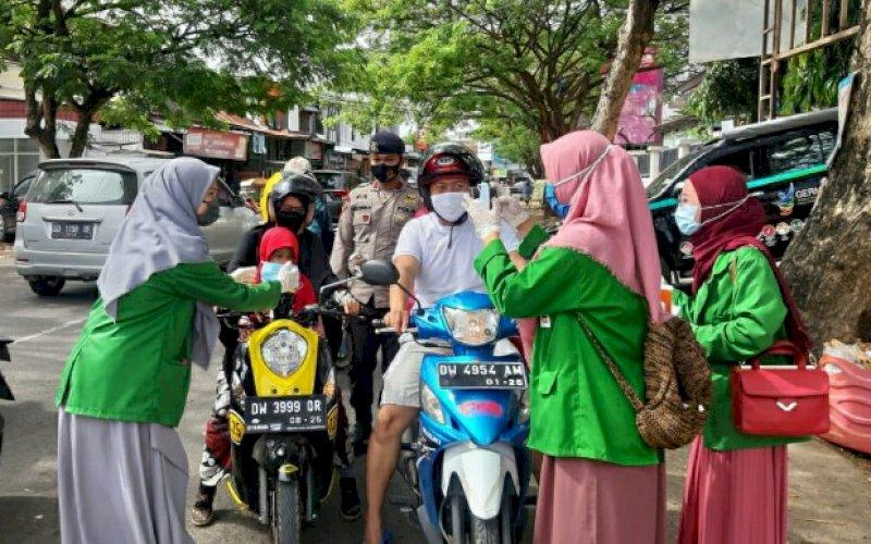 BAGI MASKER. Personel Batalyon C Pelopor Satbrimob Polda Sulsel bersama mahasiswa IAIN Kabupaten Bone menggelar kegiatan bagi-bagi masker gratis kepada para pengguna jalan di Kota Watampone, Selasa (29/9/2020). foto: istimewa