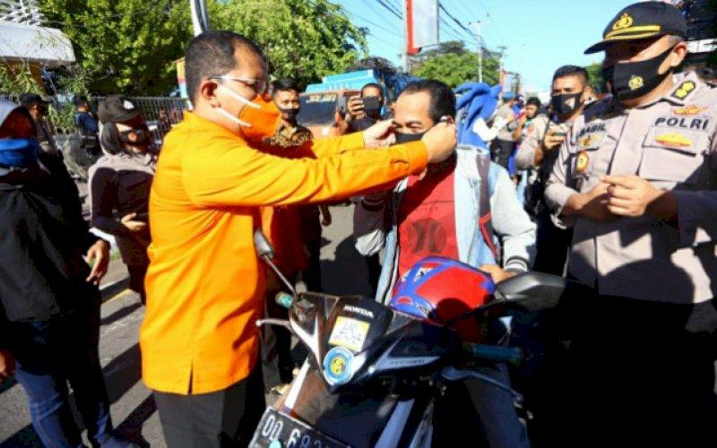 PAKAIKAN MASKER. Bakal calon Wali Kota Makassar, Mohammad Ramdhan Pomanto, memakaikan masker kepada salah satu pengendara motor pada kampanye melawan Covid-19 yang diselenggarakan Polda Sulsel di Jl Ahmad Yani, Kota Makassar, Kamis (10/9/2020). foto: istimewa