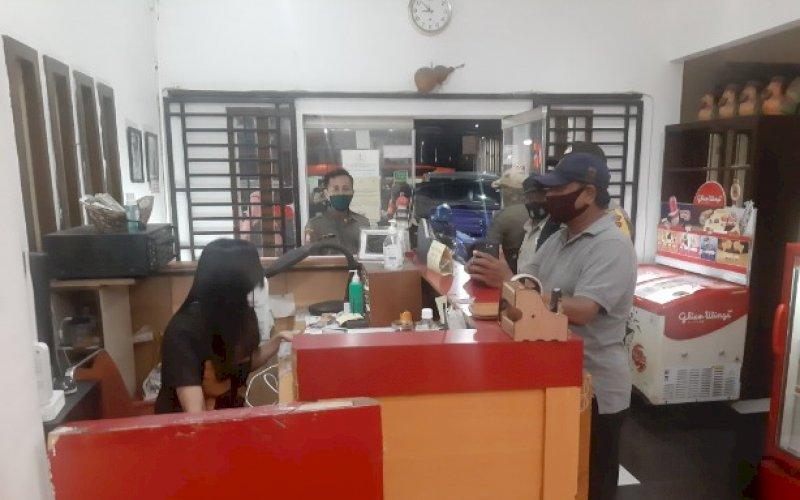 SOSIALISASI. Satgas Penegakan Disiplin Kota Makassar melakukan sosialisasi penerapan protokol kesehatan di salah satu rumah makan di Jl Gunung Latimojong, Kota Makassar, Selasa (15/9/2020) malam. foto: doelbeckz/pluz.id
