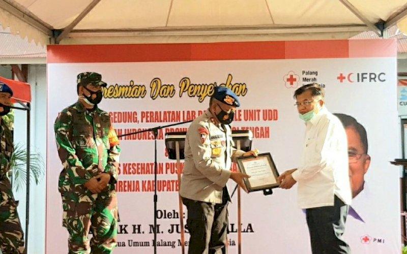 PENYERAHAN PIAGAM. Ketua PMI Pusat Jusuf Kalla (JK) menyerahkan piagam kepada Kapolda Sulteng Irjen Pol Drs Abdul Rakhman Baso SH pada kunjungannya ke Palu, Sulteng, Senin (14/12/2020). foto: istimewa