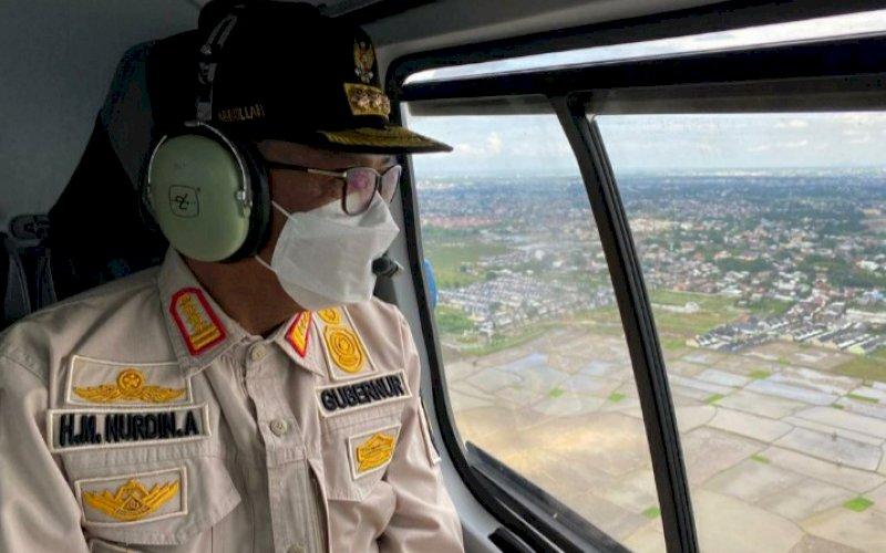 PEMANTAUAN. Gubernur Sulsel, Nurdin Abdullah, melakukan pemantauan lewat udara menggunakan helikopter milik BNPB di Kota Makassar, Gowa, Takalar, dan Jeneponto, Senin (28/12/2020). foto: istimewa