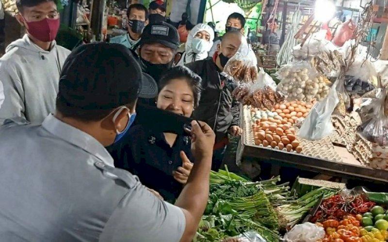 GUNAKAN MASKER. Petugas dari PD Pasar Makassar Raya Kota Makassar memasangkan masker kepada pengunjung/pembeli di salah satu pasar tradisional. foto: istimewa