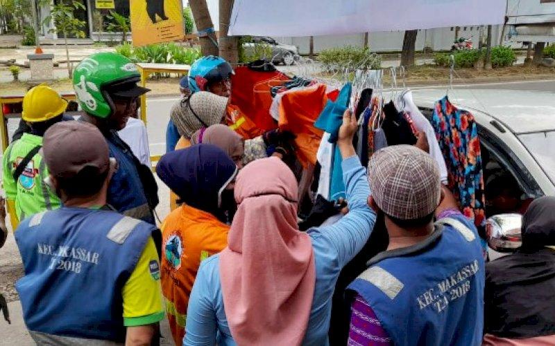 BERBAGI. Warga memilih pakaian yang disediakan gratis di Warkop Pegasus, Jl Pengayoman, Kota Makassar, Sabtu (27/3/2021). foto: tim uq pegasus