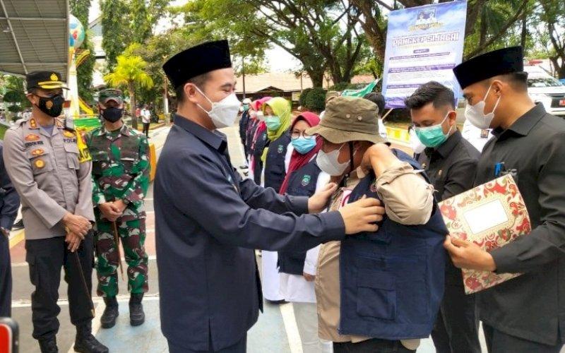 LAUNCHING. Bupati Pangkep, H Muhammad Yusran Lalogau, memasangkan rompi kepada tim medis sebagai simbol launching program Pangkep Sijagai di alun-alun Citra Mas Pangkep, Rabu (5/5/2021). foto: humas pemkab pangkep