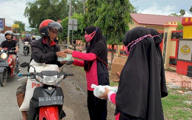 BERBAGI TAKJIL. Anggota Bhayangkari Ranting Batalyon C Pelopor membagikan takjil kepada pengendara motor, Kamis (6/5/2021). foto: humas brimob bone