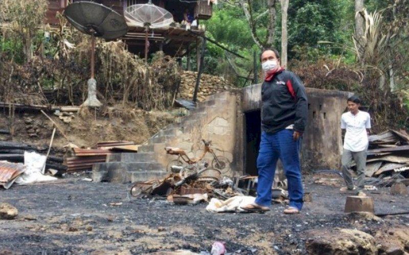 PEDULI. Anggota DPRD Provinsi Sulsel dari Fraksi PPP, Saharuddin, berjalan di antara puing kebakaran rumah di Dusun Langae, Desa Potokullin, Kecamatan Buntu Batu, Kabupaten Enrekang, Minggu (16/5/2021). foto: istimewa