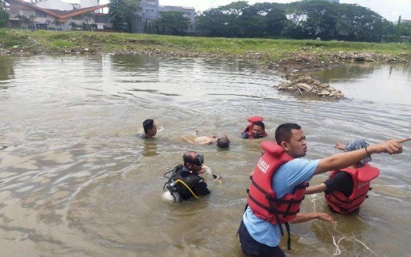PENEMUAN KORBAN. Petugas bersama warga menemukan dan mengangkat anak tenggelam dari dalam kubungan pembongkaran Stadion Andi Mattalatta Makassar, Minggu (23/5/2021). foto: istimewa