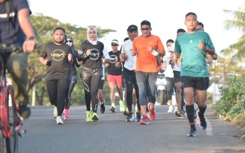 BERLARI. Menteri Pariwisata dan Ekonomi Kreatif RI, Sandiaga Salahuddin Uno (kedua kanan), menyempatkan berlari menjelajahi Makassar bersama komunitas lari NRVC (Night Run Vercity), Jumat (18/6/2021) pagi. foto: humas pemkot makassar