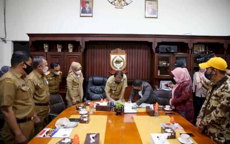 KERJA SAMA. Wali Kota Makassar, Moh Ramdhan Pomanto, menandatangani nota kesepahaman dengan KPU Kota Makassar di Balai Kota Makassar, Senin (5/7/2021). foto: istimewa