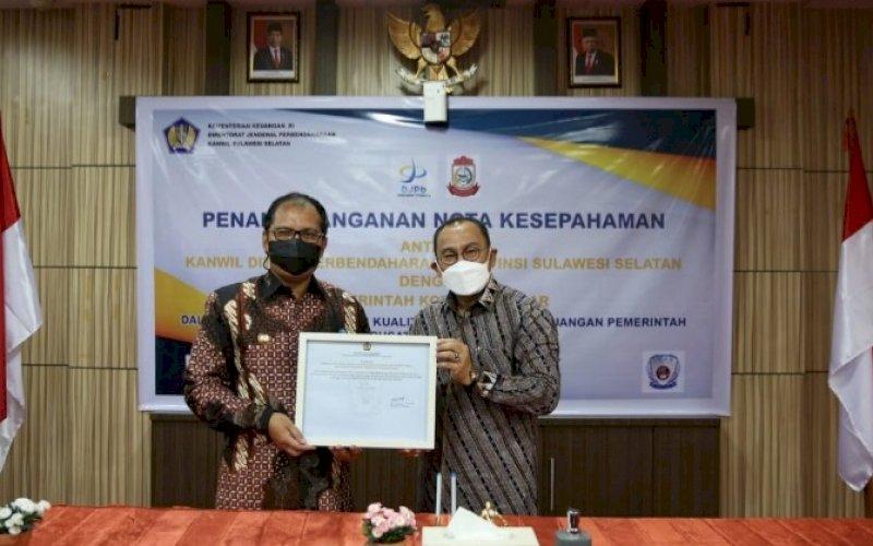 MOU. Wali Kota Makassar Moh Ramdhan Pomanto (kiri) bersama Kepala Kanwil DJPb Provinsi Sulsel Syaiful memperlihatkan nota MoU di Ruang VIP Gedung Keuangan Negara II Makassar, Kamis (8/7/2021). foto: istimewa