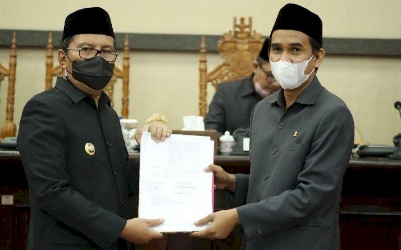 PENYERAHAN. Ketua DPRD Kota Makassar Rudianto Lallo (kanan) menyerahkan draf Laporan Pertanggungjawaban Pelaksanaan APBD 2020 Kota Makassar yang telah disahkan menjadi peraturan daerah pada rapat paripurna di DPRD Makassar, Rabu (7/7/2021). foto: istimewa