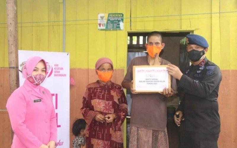 PEDULI. Danyon C Pelopor, Kompol Nur Ichsan, memimpin personel dan Bhayangkari Ranting Batalyon C Pelopor menyambangi warga kurang mampu untuk memberikan bantuan paket sembako, Jumat (9/7/2021). foto: istimewa