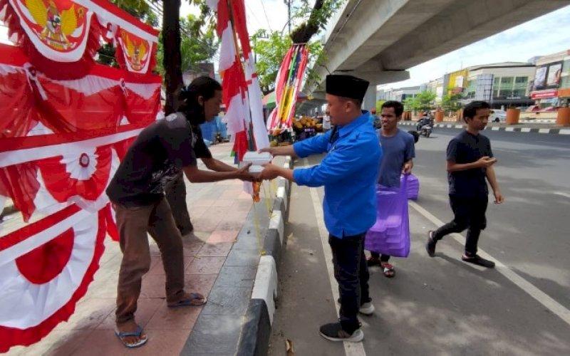 KNPI BERBAGI. Ketua DPD II KNPI Makassar, Hasrul Kaharuddin, membagikan nasi dos kepada warga dan pengguna jalan di Jl AP Pettarani, Kota Makassar, Jumat, (30/7/2021). foto: istimewa