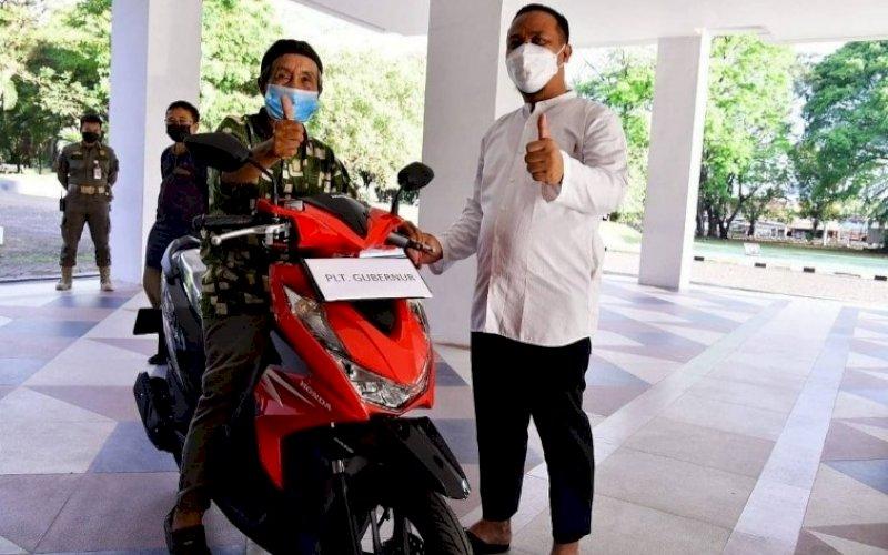 BERI HADIAH. Plt Gubernur Sulsel, Andi Sudirman Sulaiman, memberikan hadiah sebuah motor kepada Kakek Safaruddin di Kantor Gubernur Sulsel, Jumat (30/7/2021). foto: istimewa