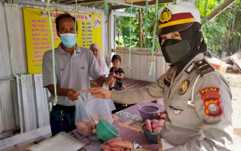 DITLANTAS PEDULI. Personel Ditlantas Polda Sulsel, menyerahkan bantuan kepada pedagang kaki lima di Kota Makassar, Rabu (4/8/2021). foto: istimewa
