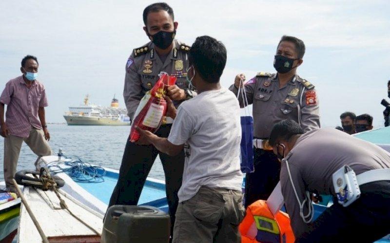 DITLANTAS PEDULI. Kasubdit Regident Ditlantas Polda Sulsel, AKBP Muh Yusuf Usman, menyerahkan bantuan kepada masyarakat nelayan dan warga Pulau Lae-lae, Kota Makassar, Jumat (6/8/2021). foto: istimewa