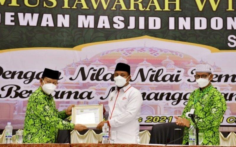 SINERGI. Ketua DMI Sulsel HM Amin Syam (kiri) menyerahkan piagam kepada Plt Gubernur Sulsel Andi Sudirman Sulaiman saat membuka kegiatan Muswil DMI Sulsel di Hotel Claro Makassar, Sabtu (14/8/2021). foto: istimewa