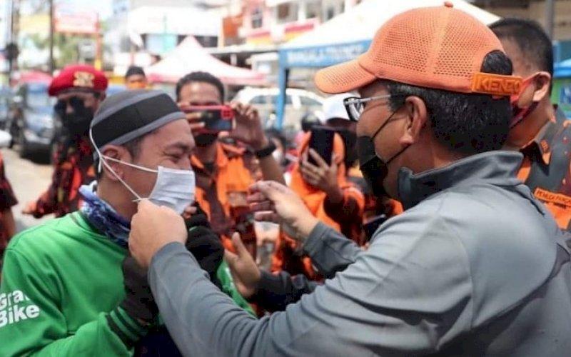 PASANGKAN MASKER. Wali Kota Makassar, Moh Ramdhan Pomanto, memasangkan masker kepada salah satu pengendara yang lewat di depan Pasar Antang, Kecamatan Manggala, Minggu (15/8/2021). foto: istimewa