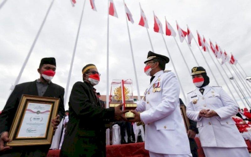 PENGHARGAAN. Wali Kota Makassar, Moh Ramdhan Pomanto, menyerahkan penghargaan kepada sembilan orang tokoh dinilai telah mengharumkan nama Makassar hingga ke tingkat nasional bahkan dunia di Anjungan Pantai Losari Makassar, Selasa (17/8/2021). foto: istimewa