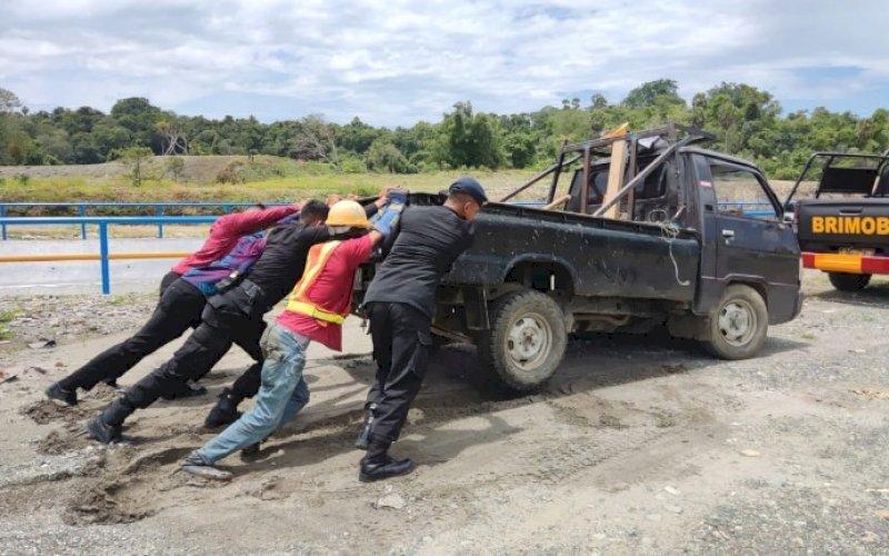EVAKUASI. Danyon C Pelopor Satbrimob Polda Sulsel, Kompol Nur Ichsan, turun langsung membantu mengevakuasi mobil pickup yang terjebak lumpur, Rabu (8/9/2021). foto: istimewa