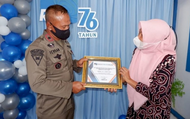 TERIMA PENGHARGAAN. Danyon C Pelopor Kompol Nur Ichsan menerima piagam penghargaan yang diserahkan langsung Koordinator RRI SP Bone Sabariah, Jumat (10/9/2021). foto: istimewa