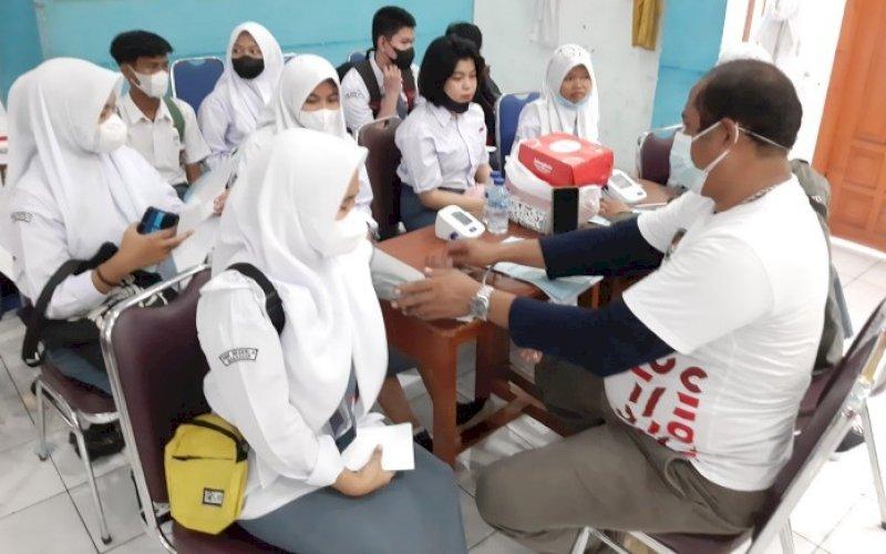 VAKSINASI. Polda Sulsel melaksanakan vaksinasi Covid-19 melalui program Roadshow Vaksinasi Pelajar, kali ini dilaksanakan di SMKN 4 Makassar, Rabu (22/9/2021). foto: doelbeckz/pluz.id
