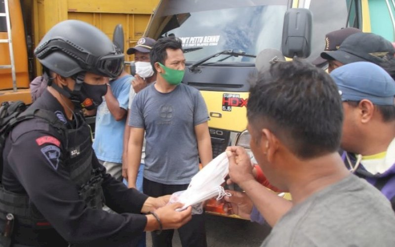 BAGI MASKER. Personel Batalyon C Pelopor Satbrimob Polda Sulsel bersama Baznas Kabupaten Bone membagikan masker kepada warga pada Patroli KRYD, Jumat (1/10/2021). foto: istimewa