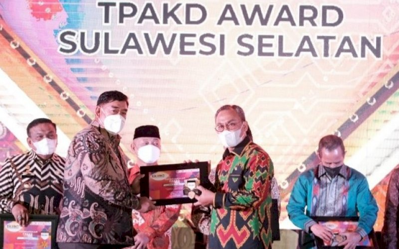 TPAKD AWARD. Sekda Provinsi Sulsel, Abdul Hayat Gani (kiri), menyerahkan TPAKD Award Sulsel kepada para penerima di sela-sela pertemuan tahunan Industri Jasa Keuangan di Toraja Utara yang dirangkaikan dengan Opening Ceremony Toraja Highland Festival, Senin (4/10/2021). foto: istimewa