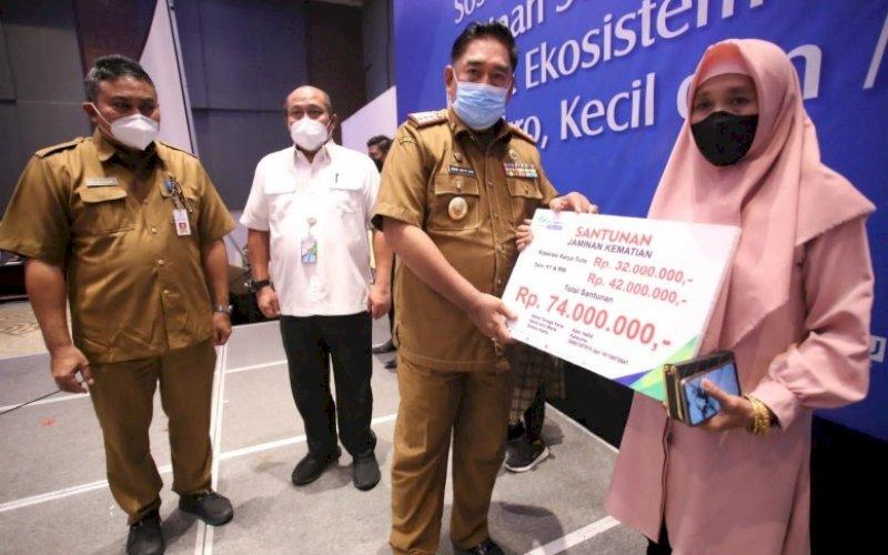 SANTUNAN. Sekda Provinsi Sulsel, Abdul Hayat Gani, menyerahkan santunan BPJS Ketenagakerjaan kepada penerima di Four Points by Sheraton Makassar, Selasa (5/10/2021). foto: istimewa